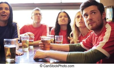 soccer fans watching football match at bar or pub - people,...