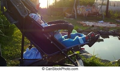 Mom cradles a baby in a stroller at the garden pond in...
