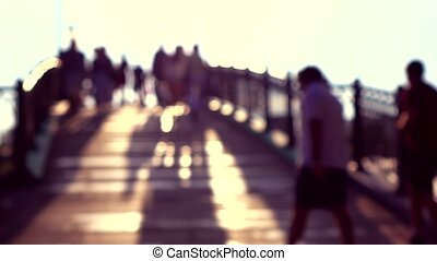 Blurred people on sunny park arched bridge. Super slow...