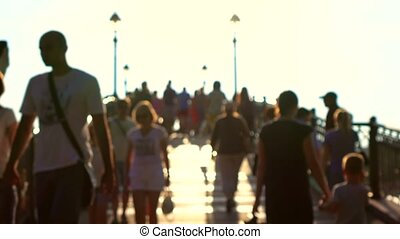 Blurred people walk on sunny park arched bridge. 4K bokeh...