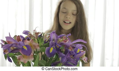 Beautiful girl enjoys bouquet of irises and alstroemeria. -...