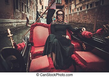 Beautiful woman in black dress with carnaval mask riding on...