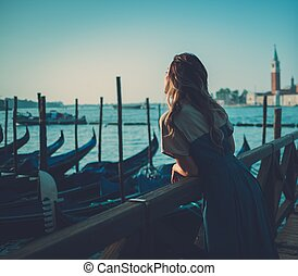 Beautiful well-dressed woman standing near San Marco square...