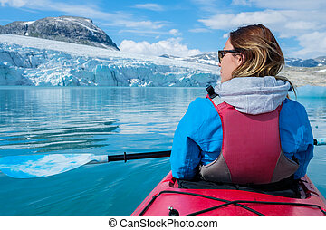 Woman kayaking on Styggvatnet glacier lake near...