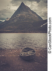 Lonely boat on the shore of wild mountain lake, Innerdalen,...