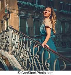 Beautiful well-dressed woman posing on a bridge over the...