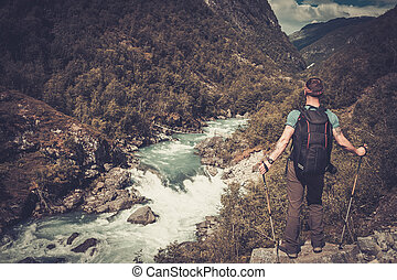 Man hiker with backpack standing on the edge of the cliff...