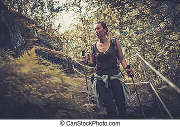 Woman hiker with backpack walking on the wild track in...
