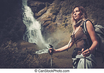 Woman hiker with backpack standing near Vettisfossen...