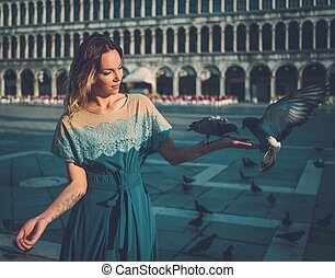 Beautiful well-dressed woman feeding pigeons on San Marco...