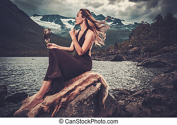 Nordic goddess in ritual garment with hawk near wild...