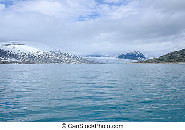 Scenic view of Styggevatnet with snowy mountains on the...