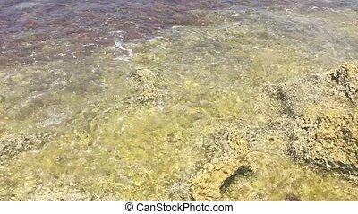 waves breaking on a rock beach - light waves breaking on a...