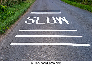 Slow Sign freshly painted on road with lines above and below...