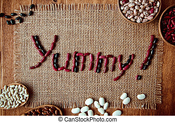 Beautiful multi-colored beans in wooden spoons on a background of burlap c posted from the bean of the word yummy