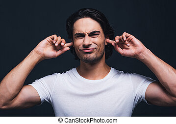 Too loud sound. Portrait of young man expressing negativity and covering ears by hands while standing against grey background