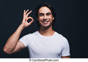 Everything is OK Happy young man gesturing OK sign and...