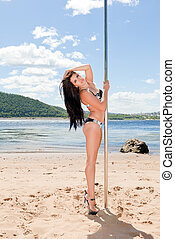 brunette in high heels standing near pole for poledance...