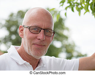 portrait of a mature man with glasses, oudoor