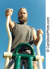 Man exercising on elliptical trainer machine - Active young...