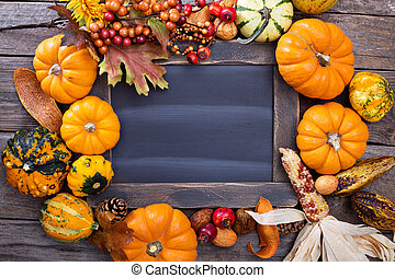 Variety of colorful decorative pumpkins around a chalkboard...