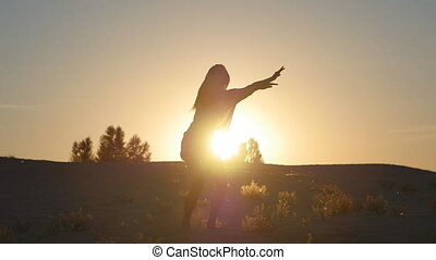 silhouette of a girl professional dancer jumping at sunset in slow motion