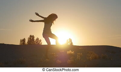 silhouette of a girl a professional dancer jumping at sunset in the desert
