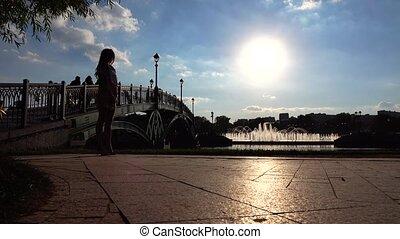 Silhouette of elegeng girl in high heels walking on sunny park embankment, 4K video