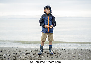 boy enjoying the rain and having fun outside on the beach a...