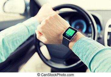 hands with music icon on smartwatch driving car - transport,...