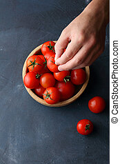 red tomatoes in bowl and man hands, food top view