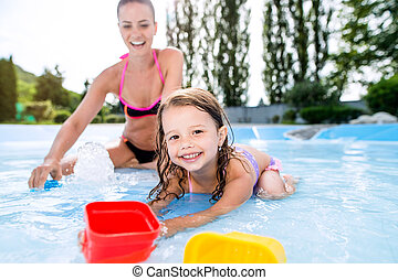 Mother and daughter in bikini having fun in aquapark. -...