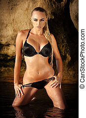 On a beach - Sexy blond girl in black bikini posing on a...