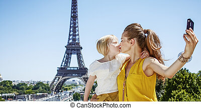 mother and daughter taking selfie and kissing in Paris -...