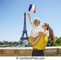 mother and child travellers rising flag in Paris, France -...