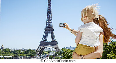 mother and child taking photo with camera against Eiffel...