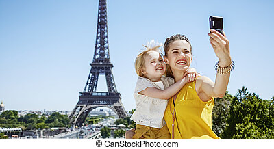 mother and daughter taking selfie with digital camera in...