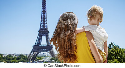 mother and child looking at Eiffel tower in Paris, France -...