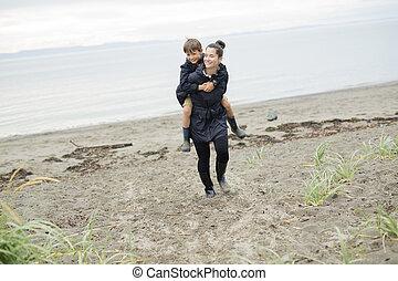 Family enjoying the rain and having fun outside on the beach...