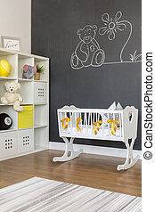 White baby cradle with yellow bowknots in blackboard room