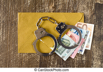 Envelope with Euro bills and handcuffs over wooden...