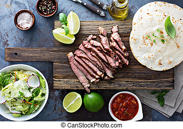 Cooking steak tacos with sliced meet and tortillas on a...
