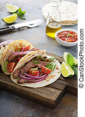 Steak tacos with sliced meet, salad and tomato salsa on a...