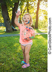 Two-year old girl stained in colors against green lawn -...