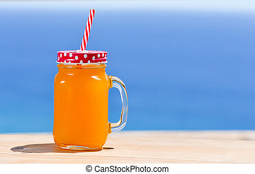 orange beverage in a handled mason jar - closeup of an...