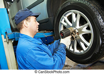 auto mechanic screwing car wheel by wrench