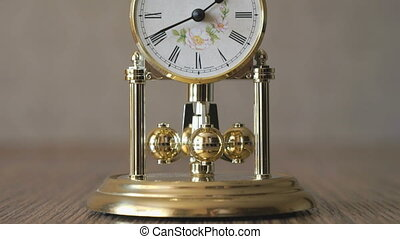 Clock with a pendulum in a form of rotating balls