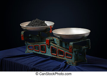 Vintage scales with a black caviar on dark background