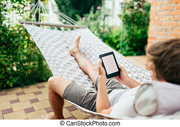 Man using e-book or tablet computer while relaxing in a hammock