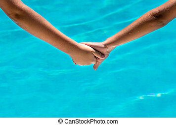 two sun tanned young people holding hands at a holiday...